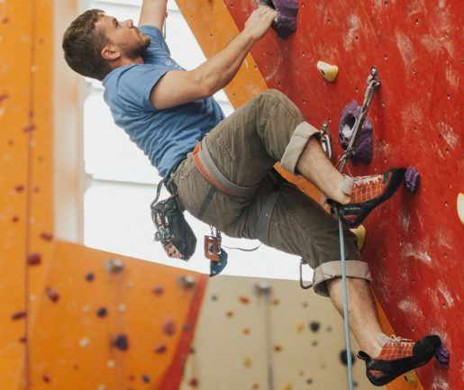 Male rock climber on indoor rock climbing gym wall.