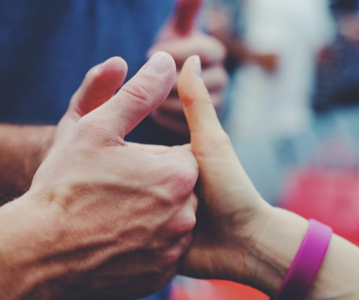 Close up of hands in a three-person thumb war-like handshake.